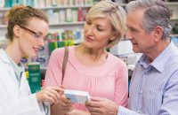 Elderly couple looking at medicine with pharmacist